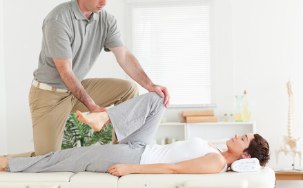 A chiropractor stretches woman's arm in his surgery