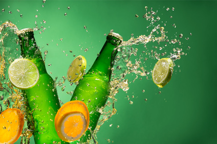 Bottles of fruit beer with splash around on green background.